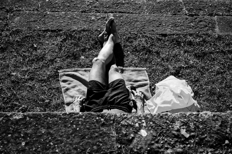 A black and white street photograph of a man sunbathing at Villa Borghese Gardens, Rome