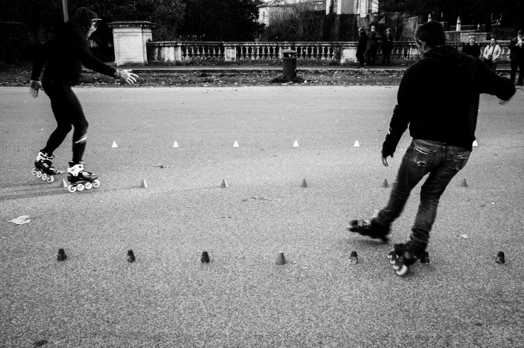 A black and white photograph of two skaters, practicing at Villa Borghese Gardens, Rome