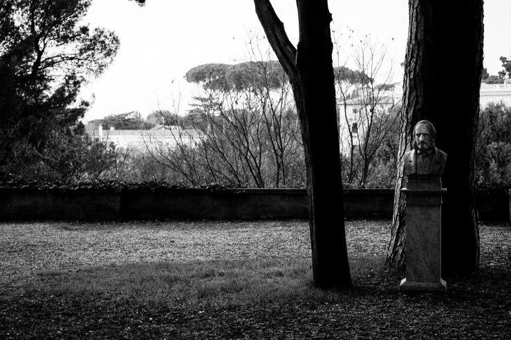 A black and white street photograph of a statue at Villa Borghese Gardens, Rome