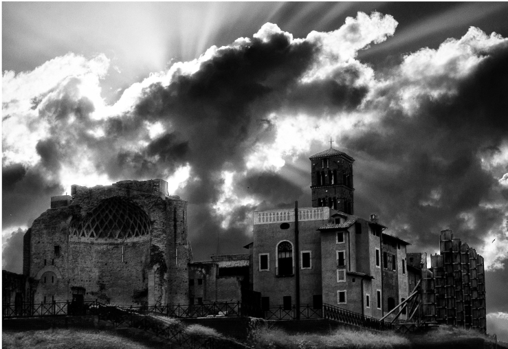 A black and white photograph of a Roman structure at Fori Imperiali, Rome. The sunlights filter through a cloud in the background.