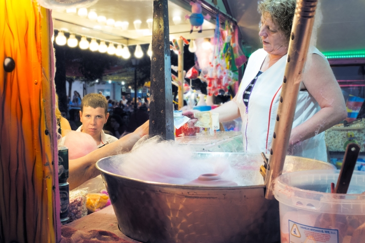 This is a street photograph of a cotton candy merchant, selling her product to some customers in Madrid