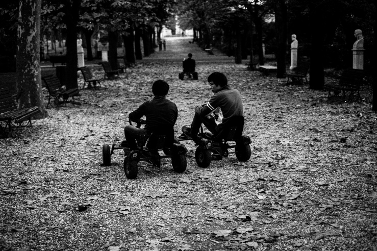 A black and white street photograph of three guys, riding kind of a bike at Villa Borghese Gardens, Rome