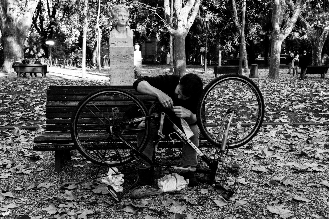 A street photograph of a man fixing his bike in Villa Borghese Gardens, Rome, Italy