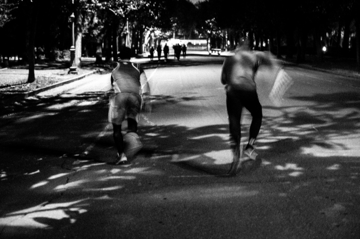 A black and white long exposure street photograph of two men training at Villa Borghese Gardens, Rome