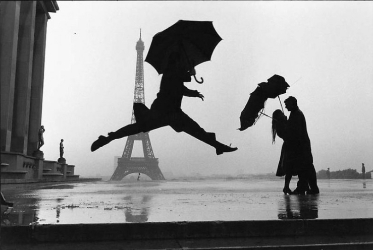 Elliott Erwitt's black and white photograph of a man holding an umbrella while jumping a pond
