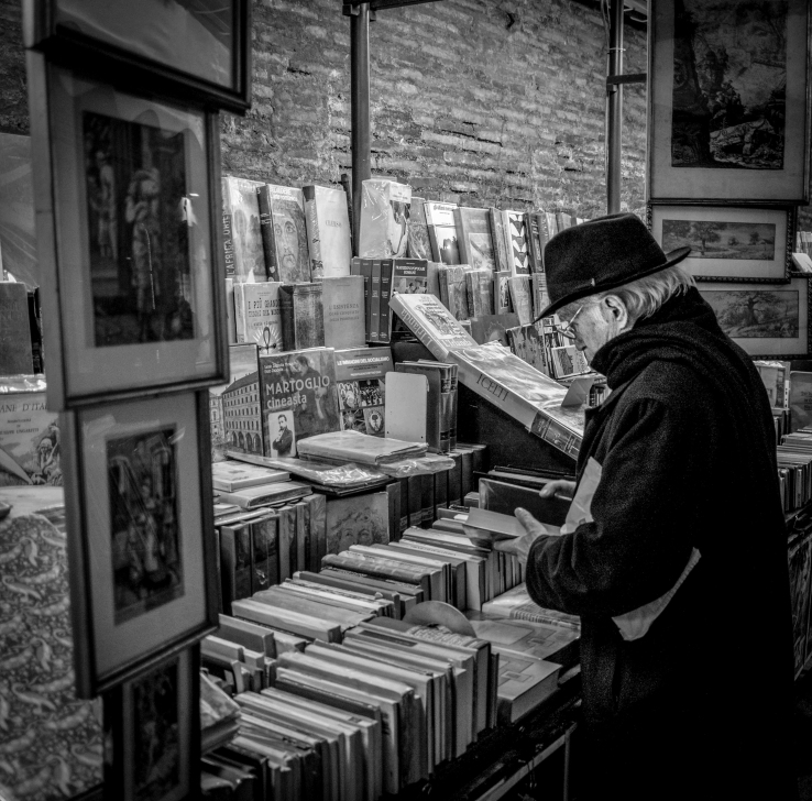 A street photograph of a man looking at a book stall in Rome