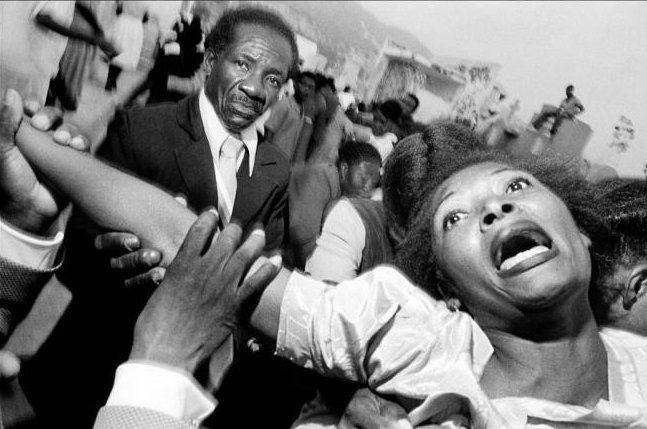 Bruce Gilden's photograph go Haiti, a black and white portrait of a lady screaming