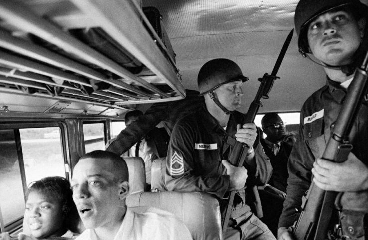 A photograph by Bruce Davidson, showing a bus used by supporters of the American Civil Rights, guarded my the army