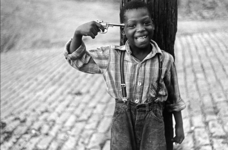 Elliott Erwitt's black and white photograph off a kid playing bu holding a gun to his head in Pittsburg
