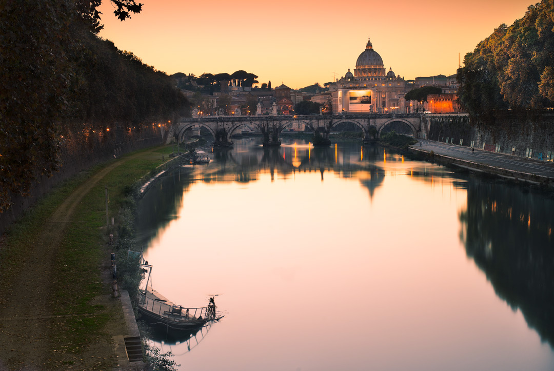 A cityscape of Saint Peter Basilica in Rome at sunset. This has been photographed using a long exposure technique to smooth out the water