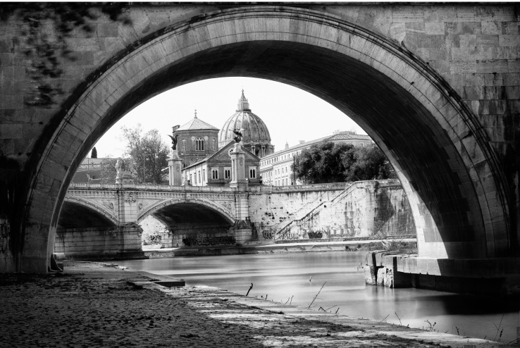 A black and white cityscape of Saint Peter Basilica, framed inside the arch of bridge